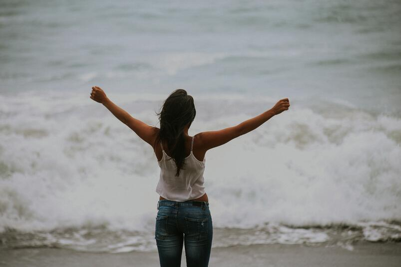girl arms outstretched looking at ocean.jpg